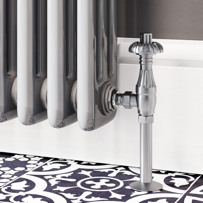 A nickel traditional radiator valve connected to a classic column radiator with some patterned floor tiles on the floor.