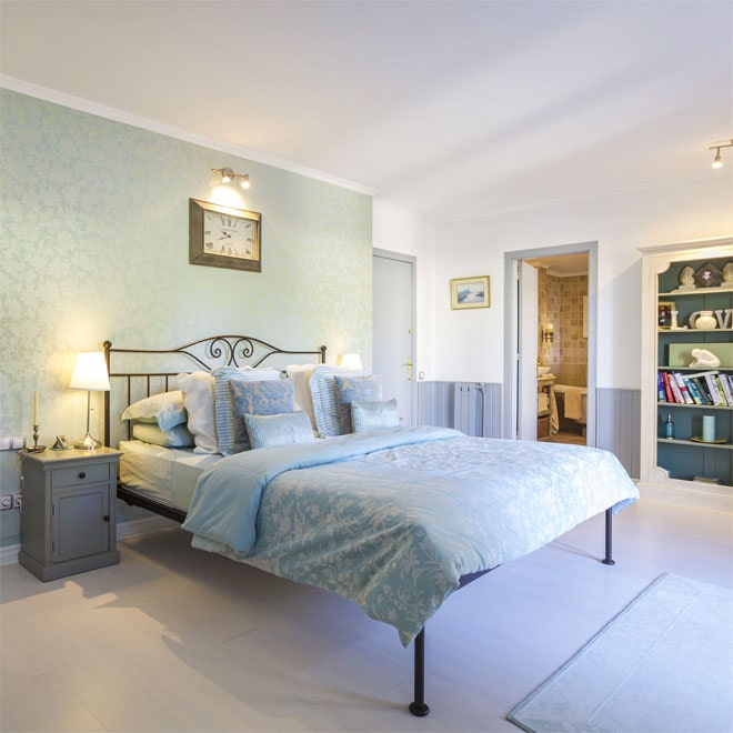 A beautiful bedroom with a feature wall behind the bed
