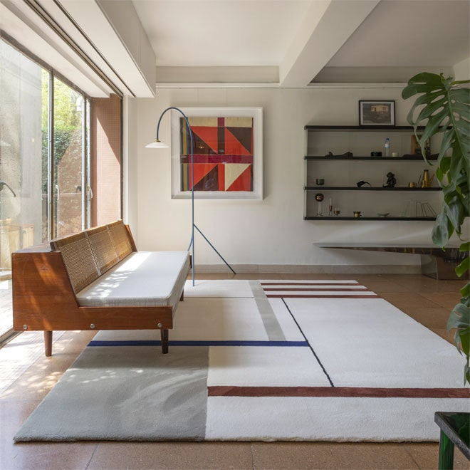 A stylish home interior with a rug placed on a wooden floor.