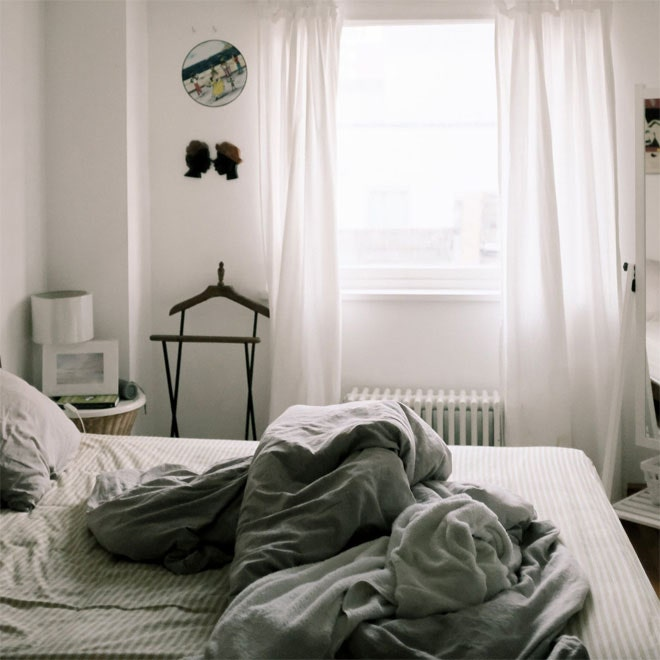 A bed in front of a radiator, but at a safe distance.