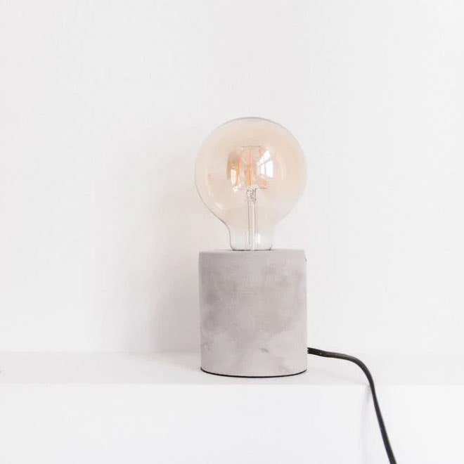 A lamp with a wire hanging down in front of a radiator